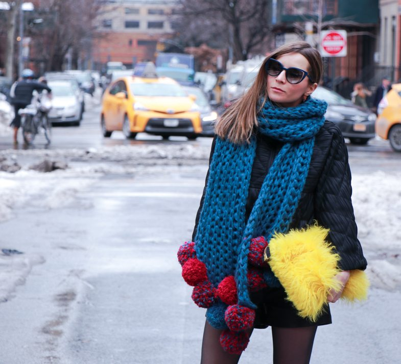 knitted scarf with pompom and coat from masaki matsuka, yellow fur clutch from OTT Dubai. New York Fashion Week Street Style Look. More NYFW Winter Layering Looks on Houseofcomil.com. Click to read more or pin to save it for later.
