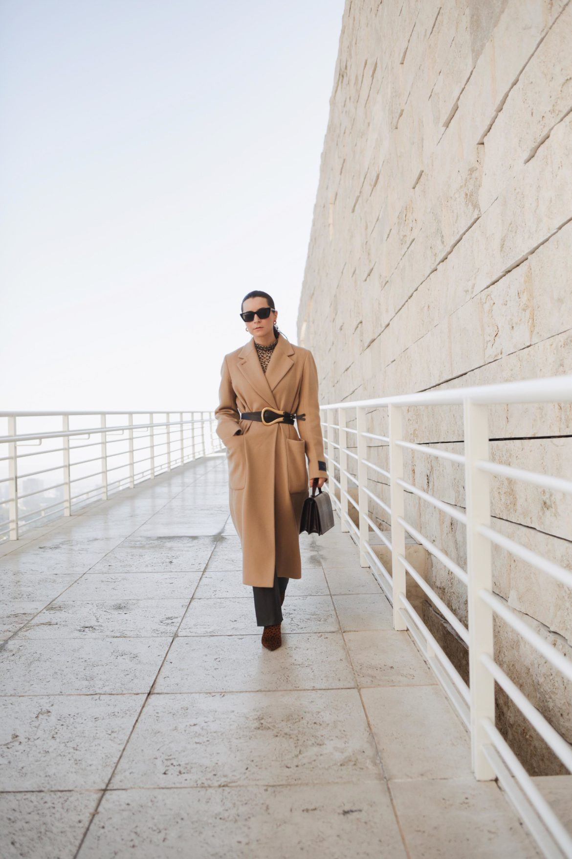 Winter style: How to style the beige wool coat. Aritzia wool coat, belt bottega veneta via Farfetch, pants equipment, AGL leopard print boots, bag yuul yie. French fashion blogger julia comil, location getty center los angeles. Fashion editorial